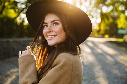 woman smiling outdoors wearing hat